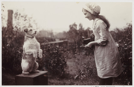 Young girl taking a photograph of a dog, c 1920s.