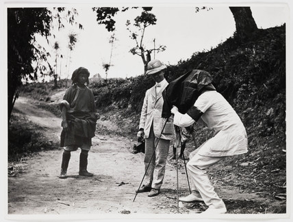 Europeans photographing an Asian man, c 1925.