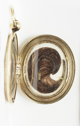 Lock of hair encased in a locket, c 1850.