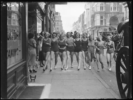Women wearing swimsuits in a London street, 1932.