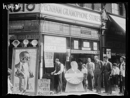 Standing outside a gramaphone shop, 1932.