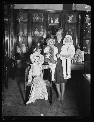 Woman with three rag dolls, 1932.