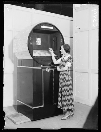 Woman demonstrating a futuristic radio set, Radiolympia, London, 1933.