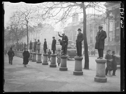 Men standing on bollards to watch a demonstration, 1934.