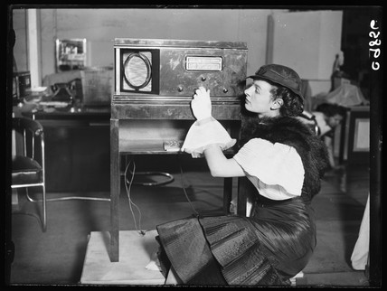 Woman inspecting an Atlas radio, Radiolympia, Olympia, London, 1934.