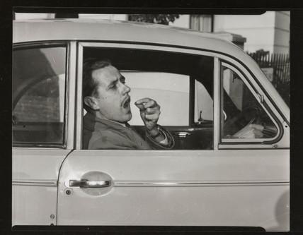 Motorist taking pills, 1953.
