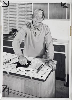 Man ironing 'Self-Stik' board laminate, c 1955
