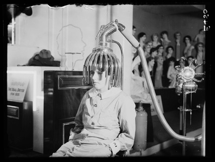 Woman sitting under a hairdryer, 9 September 1934.