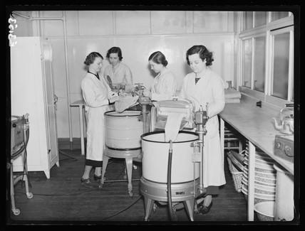 Young women using electric washing machines, 1935.