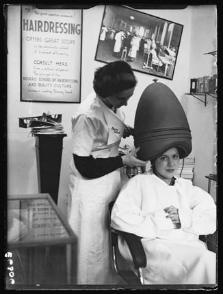 Woman sitting under a hairdryer, 1938.