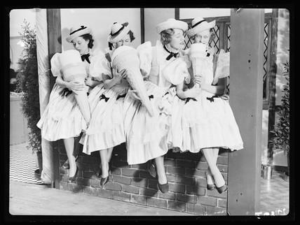 Women 'eating' giant ice cream cones, 1936.