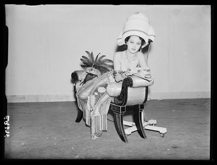 Woman under a hairdrier, 1930s.