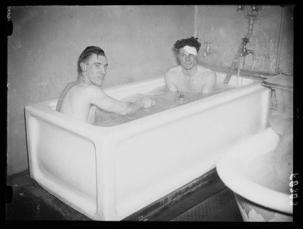 Two footballers share a bath, 1938.