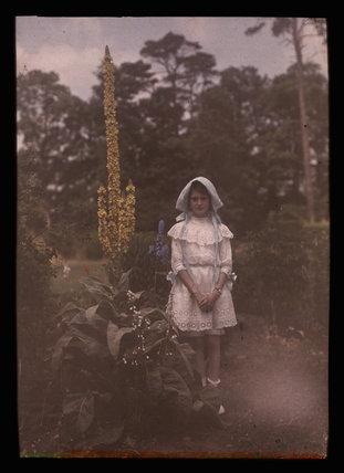 Girl standing in a garden, 1908.