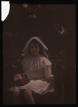 Girl sitting with flowers, 1908.