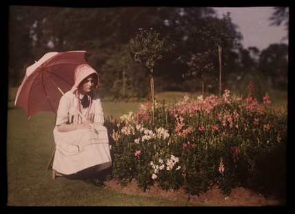 Girl with a parasol sitting by a flower bed, 1908.
