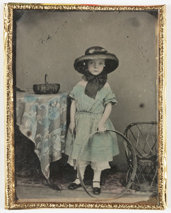 Portrait of a girl holding a hoop by a table, c 1840-1890.