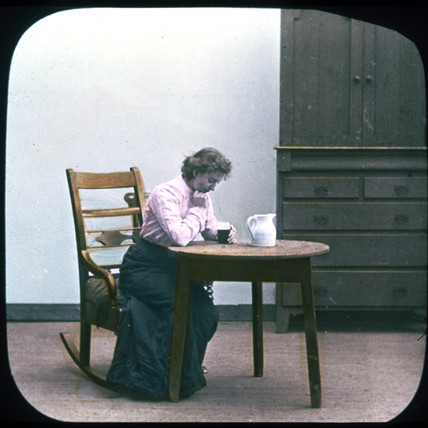 Woman with drink in rocking chair, c 1895.