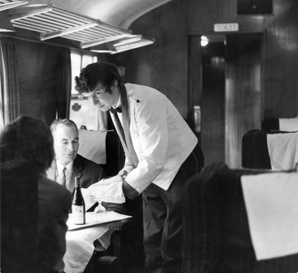 Brian Vaughan, steward, serving wine to passengers, 15 October 1971.