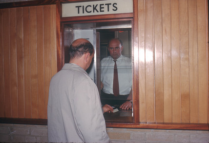 Traveller buying railway ticket, Olympia Station, London, 1963.