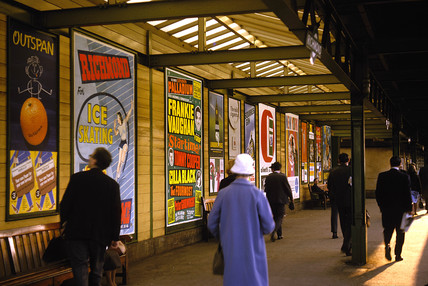 Passengers and poster advertisements on railway platform, London, 1965.