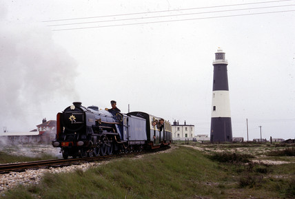 Miniature train passing a lighthouse, Dungeness, Kent, 1966.