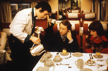 Steward serving coffee to a couple on the train, 1975-1985.
