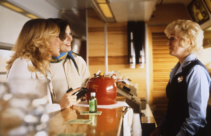 Stewardess serving two women in a buffet car, c 1980s.