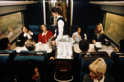 Stewardess serving coffee to smartly dressed passengers, 1975-1985.