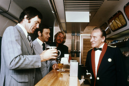 Waiter serving male passengers in buffet car, c 1970s.