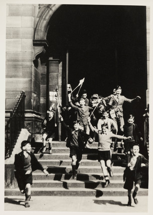 Schoolboys gleefully rushing out of school, c 1945.