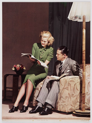 Woman reading a magazine on the arm of a man's chair, c 1940s.
