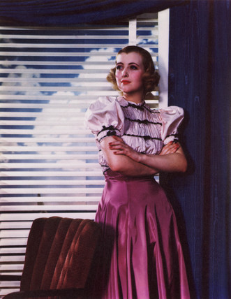 Woman standing by a window with blinds, c 1940s.
