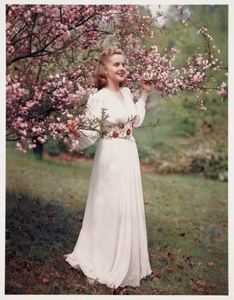 Woman modelling a dress near blossom, c 1940s.