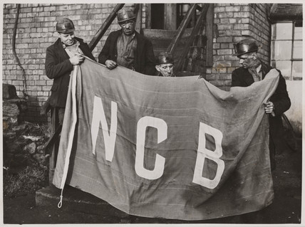 Four miners with the NCB flag, 1946.