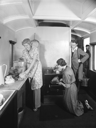 Holidaymakers preparing food inside a camping coach, 1936.
