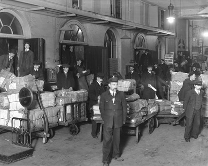 Newspapers being loaded onto a train, Paddington Station, London, c 1910.