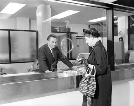 Woman buying a ticket at Liverpool Street station, London, 17 June 1964.