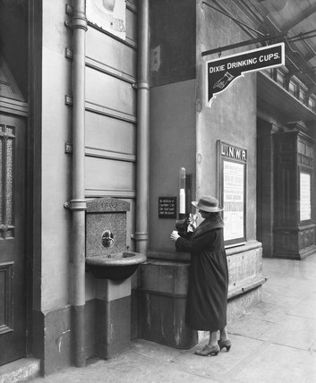 Passenger at a drinking fountain at Chester station, Cheshire, 1921.