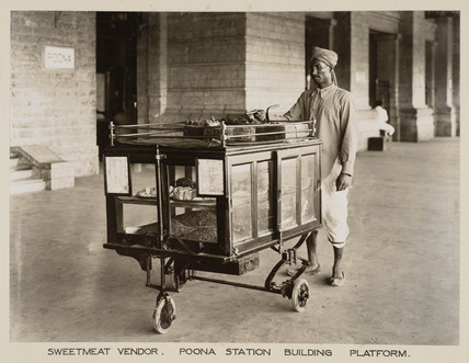 Vendor selling sweets and cakes at Poona Station, India, c 1930.