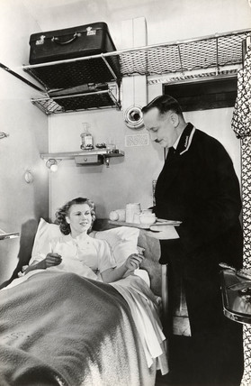 Passenger being served breakfast in bed in a sleeping car, c 1937.