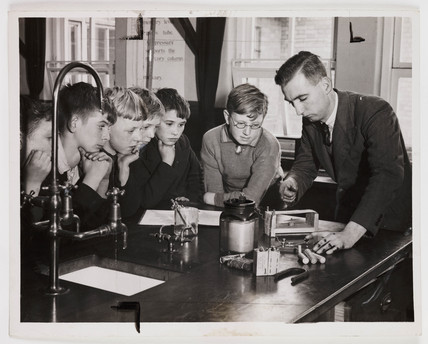 School children watching an experiment in the science laboratory, 1938.
