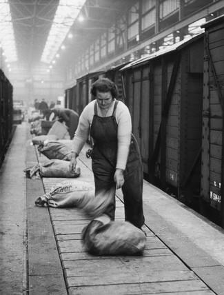 Female worker unloading a sack onto a conveyer belt, c 1950s?