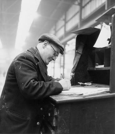 Clerk at a goods depot entering details in a ledger.