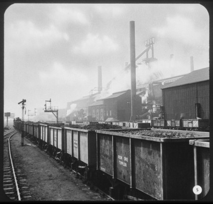 Train of iron ore tipplers at an industrial site.