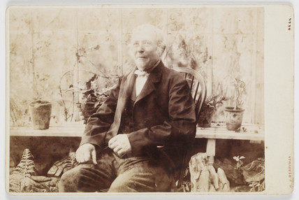 Elderly man sitting in a greenhouse, 1880s.