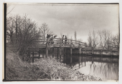 Workers return over bridge, c 1890.