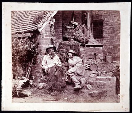 Two fishermen mending nets, c 1855.