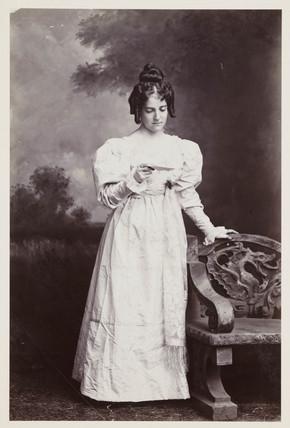 Edwardian portrait, woman in 19th-century dress reading a letter.