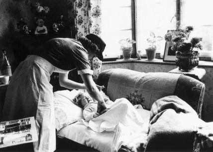 District nurse attending a sick child, November 1955.